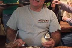 Blake grins and bears it after the previous customer had set him up by unscrewing the lid to the cheese container! This was at Hideway Pizza in Stillwater, Oklahoma.